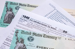 US Treasury stimulus check laying on a form 1040 tax return for 2020 to illustrate questions about qualification for payment