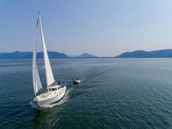 USA, Alaska, Tongass National Forest, Aerial view of Gulf 32 sailboat S/V Abuelos sailing through Frederick Sound on summer afternoon