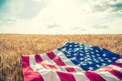USA American flag spreaded on the golden wheat field.