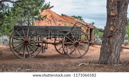 USA, Arizona, Navajo Nation, Navajo National Monument. A historic pioneer era wagon with 12 spoke wheels in front of a mud Hogan hut house.