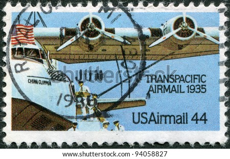 "USA - CIRCA 1985: A stamp printed in the USA, dedicated to 50th anniversary of the trans-Pacific mail flights, shows the loading of the aircraft-mail Martin M-130 ""China Clipper"", circa 1985"