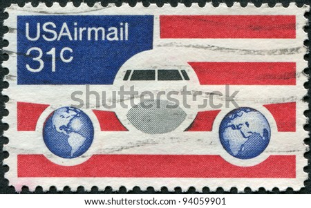 USA - CIRCA 1976: A stamp printed in the USA, shows a Plane, Globes and Flag, circa 1976