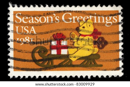 USA - CIRCA 1981 : A stamp printed in the USA shows Season's Greetings, teddy bear sled gift, circa 1981