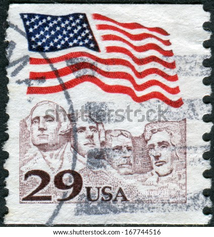 USA - CIRCA 1991: Postage stamp printed in the USA, shows the national flag over Mount Rushmore National Memorial, circa 1991