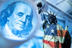 USA economy. Financial. Franklin's portrait next to statue of liberty. Statue of Liberty is painted in colors of the USA flag. Federal Reserve System of America. Concept - financial forecast for  USA