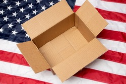 USA flag and open shipping box. Delivery from the USA