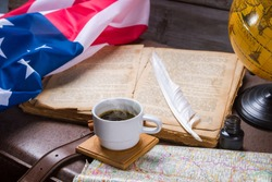 USA flag near opened book. Coffee cup and map. History of America's discovery. Tale about the bygone days.