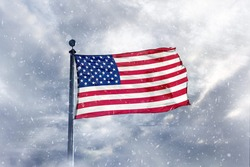 USA flag on top of mountain during snow storm