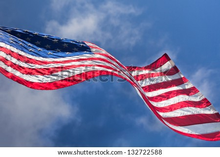 USA flag waving on the wind on cloudy sky background