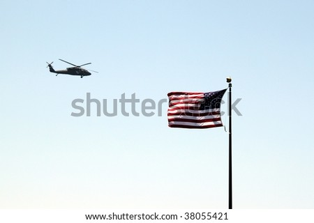 USA helicopter flying by a US flag with blue sky