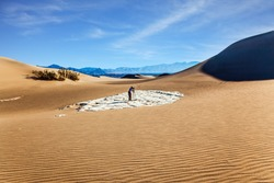 USA. Mesquite Flat Sand Dunes, Death Valley, California. Woman with photographic camera and a tripod stands among the dunes. Concept of active and photo tourism