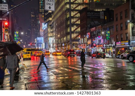 USA, New York, Manhattan. May 3, 2019. Broadway streets a rainy night. Illuminated buildings, colorful neon lights, taxi cabs, cars and people walking in the rain