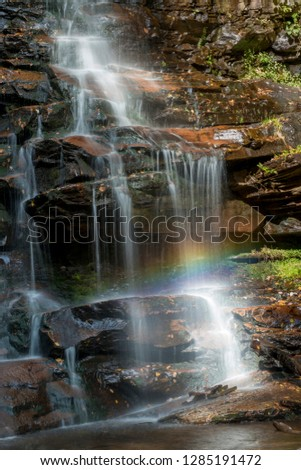 USA, Pennsylvania, Ricketts Glen State Park. Detail of water cascading down Ganoga Falls with rainbow