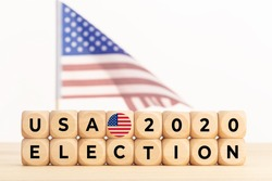 USA 2020 presidential election concept. Wooden block with text and american flag. Copy space