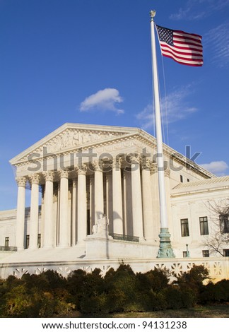 USA Supreme Court building in Washington, D.C. with an American flag and pole