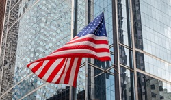 USA symbol. American flag waving in Chicago, Illinois downtown. Highrise gass buildings background.