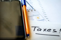 USA tax due date marked on calendar, pen and notes and smartphone calculator, focus on planning number - 17 April