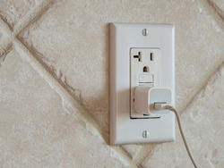 USB cell phone power adapter brick and cord in GFCI wall plug. Electrical cord and charger plug in wall outlet.