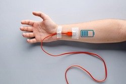 USB charge cable plugged in to a male arm with battery charging symbol. Tiredness, recharging, vitality, endurance, overwork, stamina, fatigue or life energy concept.