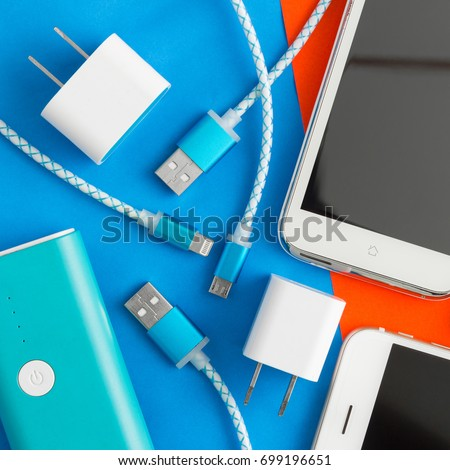 USB charging cables for smartphone and tablet in top view on blue and orange background