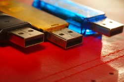 USB flash drive - black, yellow and blue, on a red background. Three used computer flash drives, ready to work. Close-up of a data memory stick, in several colors, on a bright background.