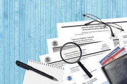 USCIS form I-9 Employment eligibility verification lies on flat lay office table and ready to fill. U.S. Citizenship and Immigration services paperwork concept. Top view