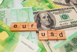 USD EUR inscription on wooden cubes on the texture of us dollars and euro banknotes