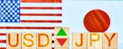 usd jpy. wooden blocks with the inscription usd jpy with arrows symbolizing the rise and fall of the currency pair against the background of national flags