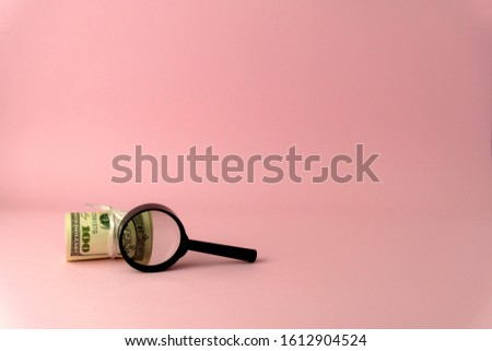 USD upon closer inspection with a magnifying glass becomes 100 USD, isolated on pink background