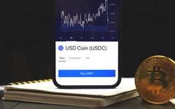 USDC USD Coin Cryptocurrency business background, crypto graphs on screen of mobile phone
