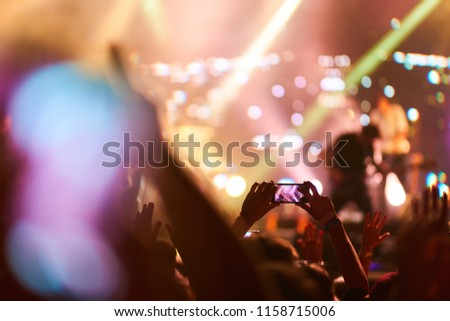 Use advanced mobile recording, fun concerts and beautiful lighting, Candid image of crowd at rock concert, Close up of recording video with smartphone, Enjoy the use of mobile photography.   #1158715006