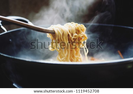 Use chopsticks to handle noodles. In a pot with smoke on an Asian stove on a junk food concept ストックフォト ©