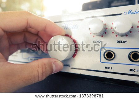 Use hand to adjust the volume at the volume control button of the amplifier. #1373398781
