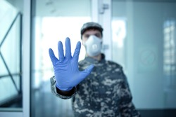 Use of military in fight against coronavirus. Soldier in military camouflage uniform standing in front of hospital entrance and showing stop gesture sign.
