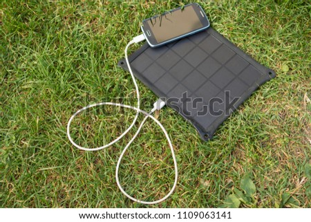 Use of renewable energy - Mobile Phone Chargers on grass in nature with Sun #1109063141