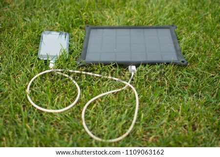 Use of renewable energy - Mobile Phone Chargers on grass in nature with Sun #1109063162