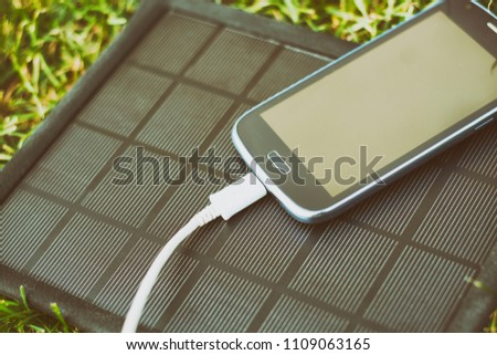 Use of renewable energy - Mobile Phone Chargers on grass in nature with Sun #1109063165