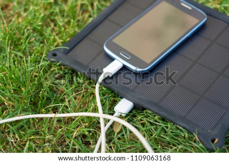 Use of renewable energy - Mobile Phone Chargers on grass in nature with Sun #1109063168