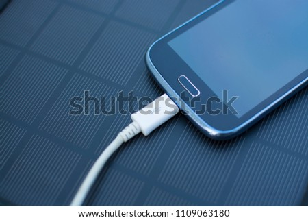Use of renewable energy - Mobile Phone Chargers on grass in nature with Sun #1109063180
