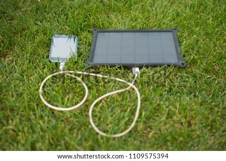 Use of renewable energy - Mobile Phone Chargers on grass in nature with Sun #1109575394