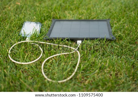 Use of renewable energy - Mobile Phone Chargers on grass in nature with Sun #1109575400
