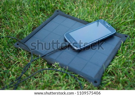 Use of renewable energy - Mobile Phone Chargers on grass in nature with Sun #1109575406