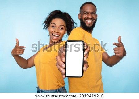 Use this new application. Cheerful black couple pointing at smartphone with blank screen, recommending mobile app, advertising your website, mockup for design. Selective focus