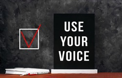 Use Your Voice text sign on black chalkboard with white notebok and red pen on dark background. Message written on blackboard display. Vote elections concept. Make the political choice.