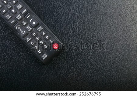 Used and dirty tv remote control put on the black color leather surface background represent the tv technology related.