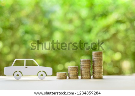 Used and second hand vehicle / car or auto loan, financial concept : Sedan car and rows of coins on a table, depicts money loan or borrowing fund to buy a new or old car for personal or individual use