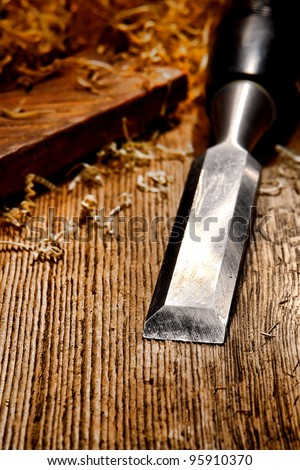 Used and worn carpenter wood chisel tool with loose shavings on old weathered distressed wooden board workbench in a vintage carpentry woodworking workshop