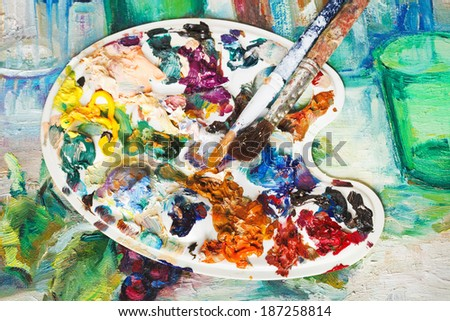 used artistic pallette with oil paints and paintbrushes on picture canvas