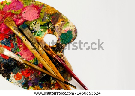 Used Artists paintbrushes with different  sizes lying on dirty artistic palette, on white background with free space on right, close up, no one, background for creative art design