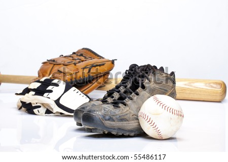 Used baseball cleats against a glove, softball, bat, and batting gloves on a white background
